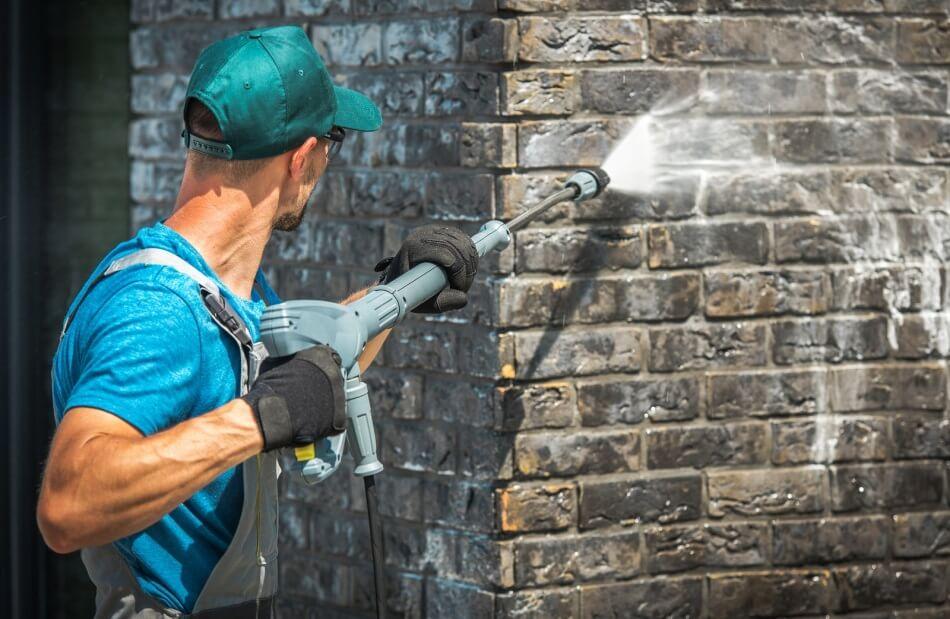Man pressure washing a brick wall - Hot Water Pressure Washer